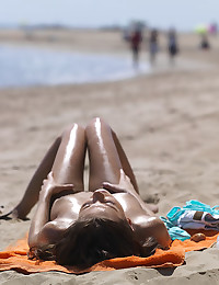 The topless girl is catching some sun at the beach and she looks lovely.