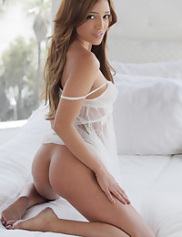 Melanie exhibits her gorgeous figure on the bed.