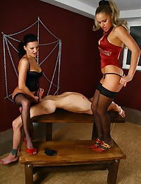 Bound slave receives a handjob from one of his mistresses while mastering his oral skills on the second one's pussy