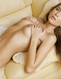 Stacey plays with her body lying on the couch.