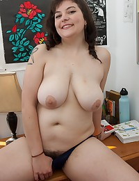Hairy newcomer Esther sits back on her chair and opens her soft creamy thighs. With her legs spread wide, she reaches down and plays with her dark hairy pussy.