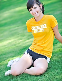 The young babe is in her workout shorts and a t-shirt as she models in the grass.
