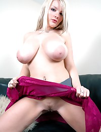 In Bed with Faith - Slutty big breasted blonde posing on a black sofa