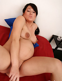 Pregnant beauty stripping naked in bed and fucking her plump pussy with a long glassy dildo