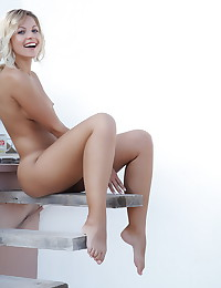 Legs open and pretty shaved pussy is shown as the blonde poses