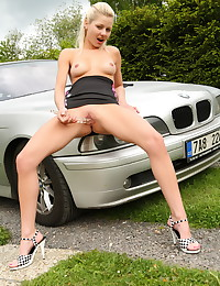 The dress is short and she sits on the car and teases with her ass and tits