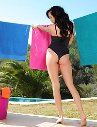 Her black one piece swimsuit is tight against her all natural body