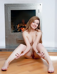 Gorgeous blonde hottie naked by the fireplace.